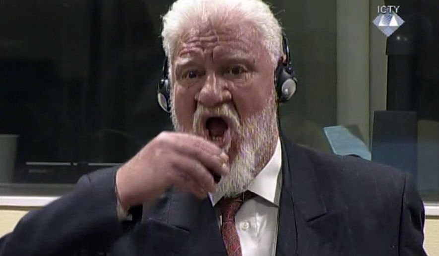 "In this photo provided by the ICTY on Wednesday, Nov. 29, 2017, Slobodan Praljak brings a bottle to his lips, during a Yugoslav War Crimes Tribunal in The Hague, Netherlands. Praljak yelled, ""I am not a war criminal!"" and appeared to drink from a small bottle, seconds after judges reconfirmed his 20-year prison sentence for involvement in a campaign to drive Muslims out of a would-be Bosnian Croat ministate in Bosnia in the early 1990s. (ICTY via AP)"