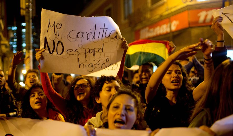 """Protesters shout slogans with one holding a sign that reads in Spanish: """"My constitution is not toilet paper"""" in La Paz, Bolivia, on Wednesday. Bolivia's highest court cleared the way for President Evo Morales to run for a fourth term in 2019. (Associated Press)"""