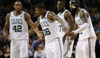 Boston Celtics' Marcus Smart (36) congratulates Al Horford (42) and Kyrie Irving during the fourth quarter of Boston's 108-97 win over the Philadelphia 76ers in an NBA basketball game in Boston Thursday, Nov. 30, 2017. (AP Photo/Winslow Townson)