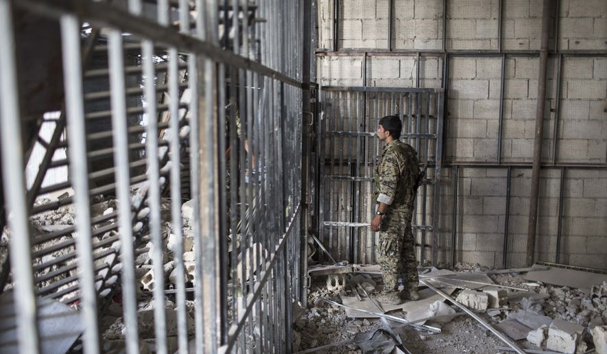 "A members of the U.S.-backed Syrian Democratic Forces (SDF) walk inside a prison built by Islamic State fighters at the stadium that was the site of Islamic State fighters' last stand in the city of Raqqa, Syria, Friday, Oct. 20, 2017. The SDF on Friday declared from the stadium during a ceremony the ""total liberation"" of Raqqa, the capital of the Islamic State for more than three years. (Photo/Asmaa Waguih)"