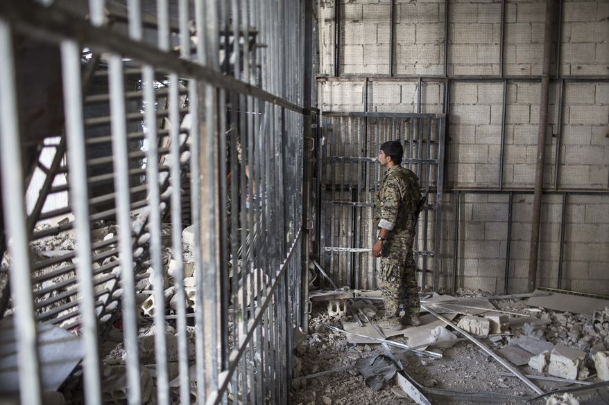"""A members of the U.S.-backed Syrian Democratic Forces (SDF) walk inside a prison built by Islamic State fighters at the stadium that was the site of Islamic State fighters' last stand in the city of Raqqa, Syria, Friday, Oct. 20, 2017. The SDF on Friday declared from the stadium during a ceremony the """"total liberation"""" of Raqqa, the capital of the Islamic State for more than three years. (Photo/Asmaa Waguih)"""