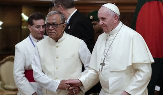 Bangladesh President Abdul Hamid, left, holds hands with Pope Francis as he accompanies at the end of their meeting at the presidential palace, in Dhaka, Bangladesh, Thursday, Nov. 30, 2017. (AP Photo/Andrew Medichini)