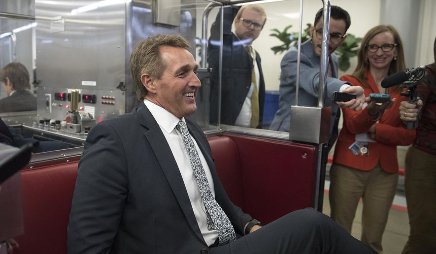 Sen. Jeff Flake, R-Ariz., talks with media as he boards the subway on Capitol Hill in Washington, Thursday, Nov. 30, 2017. (AP Photo/Carolyn Kaster)