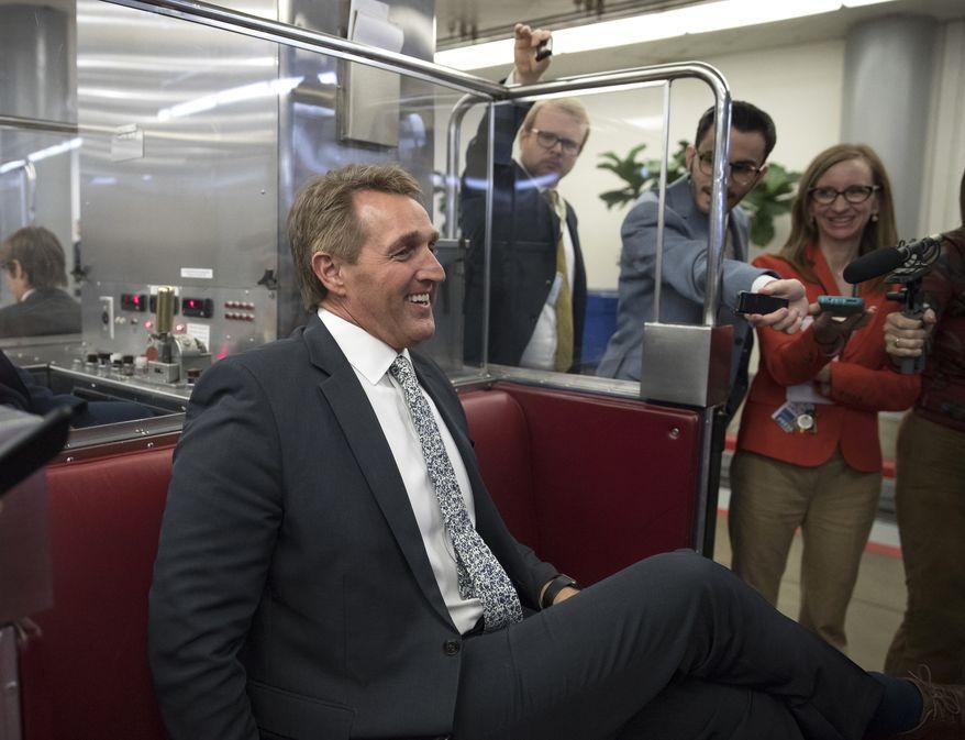Sen. Jeff Flake, R-Ariz., talks with media as he boards the subway on Capitol Hill in Washington, Thursday, Nov. 30, 2017. (AP Photo/Carolyn Kaster)