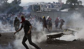 Supporters of opposition presidential candidate Salvador Nasralla throw rocks at police who fired tear gas as they clash near the institute where election ballots are stored in Tegucigalpa, Honduras, Thursday, Nov. 30, 2017. Protests are growing as incumbent President Juan Orlando Hernandez emerged with a growing lead for re-election following a reported computer glitch that shut down vote counting for several hours. (AP Photo/Rodrigo Abd)