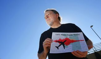 FILE - In this Feb. 6, 2015. file photo, Steve Dreiseszun, a resident of the F.Q. Story historic district in Phoenix, holds a graphic of the increased noise brought on by airplanes flying along new flight paths out of Phoenix Sky Harbor International Airport. The city of Phoenix and the Federation Aviation Administration said Thursday, Nov. 30, 2017, they have come up with a plan aimed at resolving a flap over noisy takeoffs and landings that followed changes in flight procedures at the airport three years ago. (AP Photo/Ross D. Franklin, File)