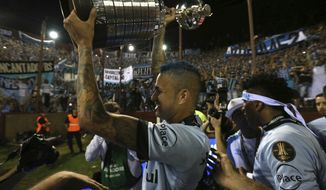 Brazil's Gremio soccer player Luan raises his team's trophy after winning the Copa Libertadores championship following a game with Argentina's Lanus in Buenos Aires, Argentina, Wednesday, Nov. 29, 2017. (AP Photo/Esteban Felix)