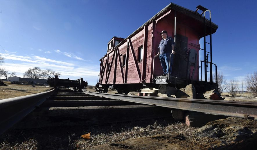 Lester Coburn and other members of the Rocky Mountain Railroad Heritage Foundation are getting closer to their dream of opening up a railroad museum at the old station in Calhan, Colo. Coburn stands at the back of a caboose that was donated to the museum, Sunday, Nov. 27, 2017. The caboose was originally a boxcar, but was made into a caboose in the 1920's. It was delivered to the site on Saturday and will be lifted by crane onto the tracks as soon as they are able to get the funds to complete that step. (Jerilee Bennett/The Gazette via AP)