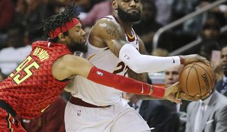 Atlanta Hawks forward DeAndre' Bembry, left, defends against Cleveland Cavaliers forward LeBron James during the first half of an NBA basketball game, Thursday, Nov. 30, 2017, in Atlanta. (Curtis Compton/Atlanta Journal-Constitution via AP)