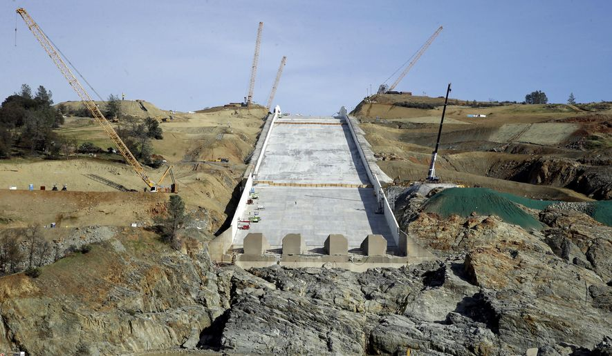 Cranes sit on the sides of the Oroville Dam spillway, Thursday, Nov. 30, 2017, in Oroville, Calif. California water officials and the construction manager said Thursday, that recently found hairline cracks on the spillway are normal and expected in reinforced concrete because it shrinks as it cures. (AP Photo/Rich Pedroncelli)