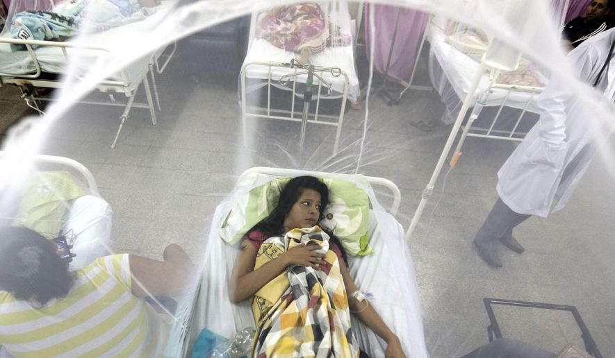 FILE - In this Friday, Feb. 5, 2016 file photo, Nadia Gonzalez, enclosed in a mosquito net, recovers from a bout of dengue fever at a hospital in Luque, Paraguay. Drugmaker Sanofi said Thursday, Nov. 30, 2017, that its dengue vaccine _ the world's first _ could put people at risk of severe disease if they haven't previously been infected, according to new long-term data. (AP Photo/Jorge Saenz, File)