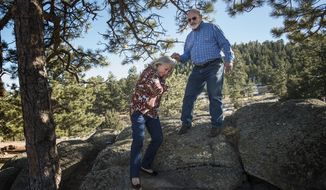 AVANCE FOR USE SATURDAY, DEC. 2 - In this Monday, Nov. 13, 2017 photo, Al Judd helps his wife Dee down from a rock outcropping near their home in the Glacier View Meadows neighborhood near Livermore, Colo. (Timothy Hurst/The Coloradoan via AP)