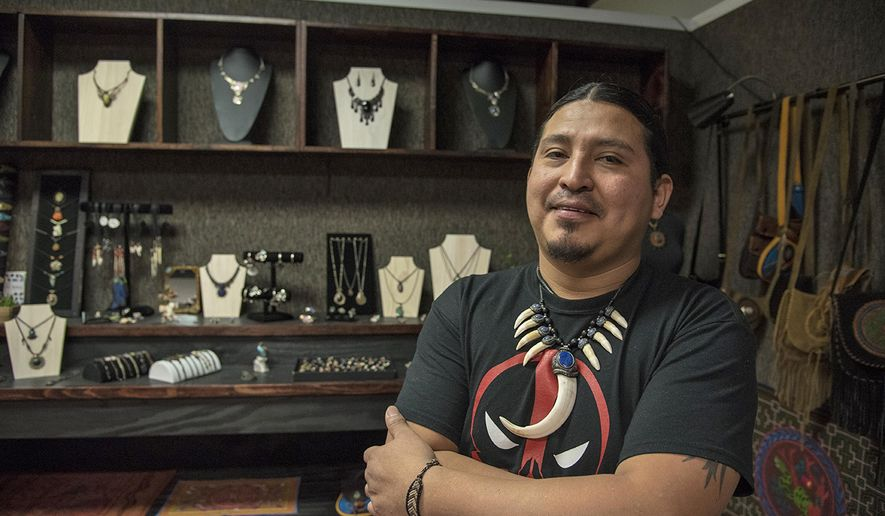 In this Nov. 20, 2017 photo, artist Luis Villa, who came to the United States in 2015, stands in  his new store, Asiri Handcrafted in Galesburg, Ill. Villa began working with handcrafted art in the country of Peru, crafting jewelry and weaving clothing to create his own forms of art. Though he had experience selling it in Peru, his new store, is his first attempt at owning and operating an official store space. (Mitch Prentice/The Register-Mail, via AP)/