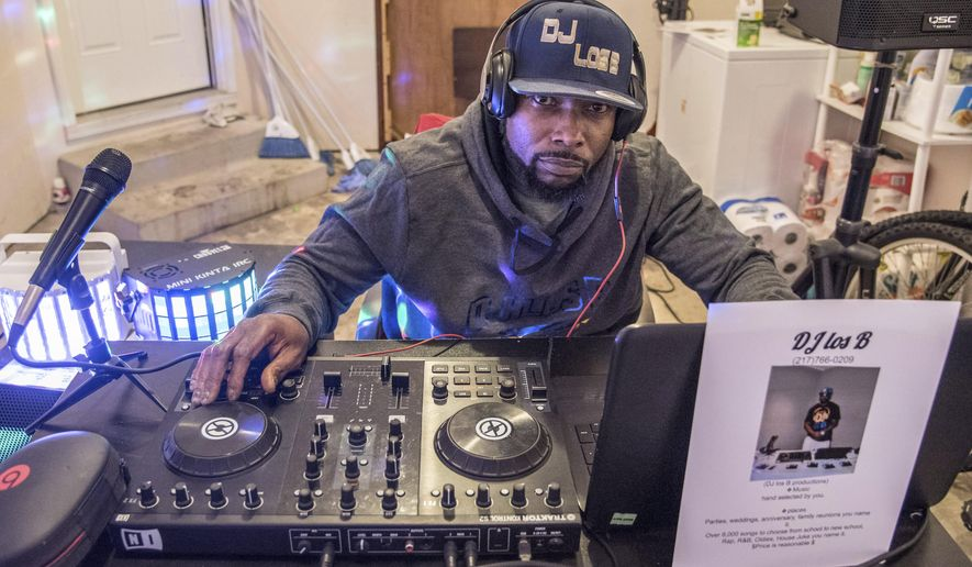 In this Nov. 20, 2017 photo, Carlos Mosley poses in his garage with his DJ equipment, in  Champaign, Ill. Mosley has had numerous run ins with the law involving drugs and alcohol but after 17 months of sobriety, the 40-year-old husband and father is about to graduate from Champaign County's drug court program, and is starting a DJ Business. (Holly Hart/The News-Gazette via AP)