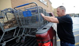 This photo taken April 17, 2017, shows Canton City Ward 3 Councilman Jason Scaglione returning shopping carts collected from his neighborhood to WalMart on Tuscarawas Street West in Canton, Ohio. (Julie Vennitti/The Canton Repository via AP)