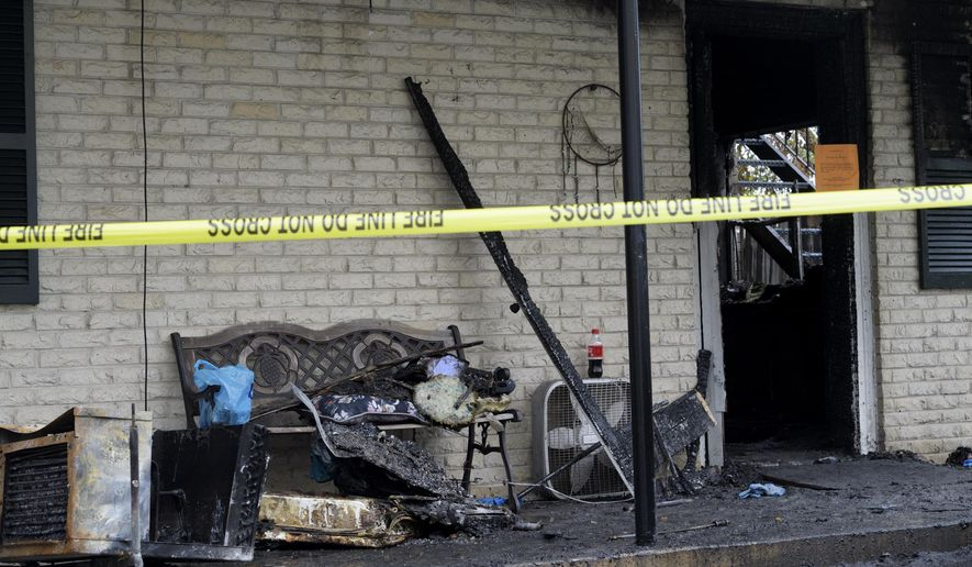 Burned items and a bench are seen in front of an apartment after a fire in Metairie, La., Thursday, Nov. 30, 2017.  Louisiana officials say an early morning fire has killed an 82-year-old man and his 56-year-old son.   (Max Becherer/The Advocate via AP)