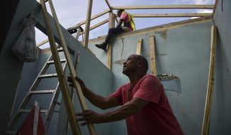 Pedro Deschamps helps workers hired by FEMA to carry out the installation of a temporary awning roof at his house, which suffered damage during Hurricane Maria, in San Juan, Puerto Rico, Wednesday, Nov. 15, 2017. A newly created Florida company with an unproven record won more than $30 million in contracts from the Federal Emergency Management Agency to provide emergency tarps and plastic sheeting for repairs to hurricane victims in Puerto Rico. Bronze Star LLC never delivered those urgently needed supplies, which even months later remain in demand on the island.   (AP Photo/Carlos Giusti)