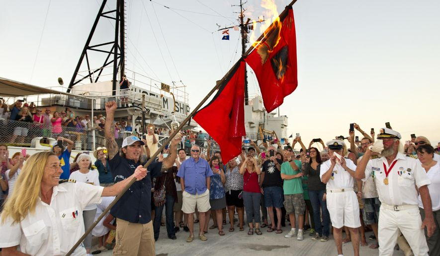 In this photo provided by the Florida Keys News Bureau, Mary Martin, left, holds burning hurricane warning flags set on fire to symbolize the end of the 2017 Atlantic Basin hurricane season Thursday, Nov. 30, 2017, in Key West, Fla. The ceremony came after a turbulent 2017 season that included three major hurricanes -- Harvey, Irma and Maria -- that pummeled parts of the U.S. and Puerto Rico. (Rob O'Neal/Florida Keys News Bureau via AP)