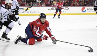 Washington Capitals center Evgeny Kuznetsov (92), of Russia, reaches for the puck in front of Los Angeles Kings defenseman Drew Doughty (8) during the second period of an NHL hockey game, Thursday, Nov. 30, 2017, in Washington. (AP Photo/Nick Wass)