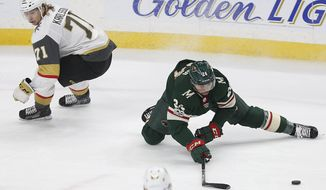 Minnesota Wild's Matt Dumba (24) tries to gain control of the puck as Vegas Golden Knights' William Karlsson (71) skates behind him in the first period of an NHL hockey game Thursday, Nov. 30, 2017, in St. Paul, Minn. (AP Photo/Stacy Bengs)