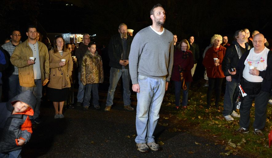 Josh Corney and about two dozen supporters stand for the playing of Taps for the last time at Corney's 49 Glen Ave. home in Glen Rock, Thursday Nov. 30, 2017. Corney, a lieutenant commander in the Navy, has been playing a 57-second recording from his home just before 8 p.m. nightly for about two years now. (John A. Pavoncello /York Dispatch via AP)
