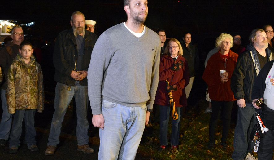 Josh Corney and about two dozen supporters stand for the playing of Taps for the last time at Corney's 49 Glen Ave. home in Glen Rock, Thursday Nov. 30, 2017. Corney, a lieutenant commander in the Navy, has been playing a 57-second recording from his home just before 8 p.m. nightly for about two years now. ( John A. Pavoncello /York Dispatch via AP)