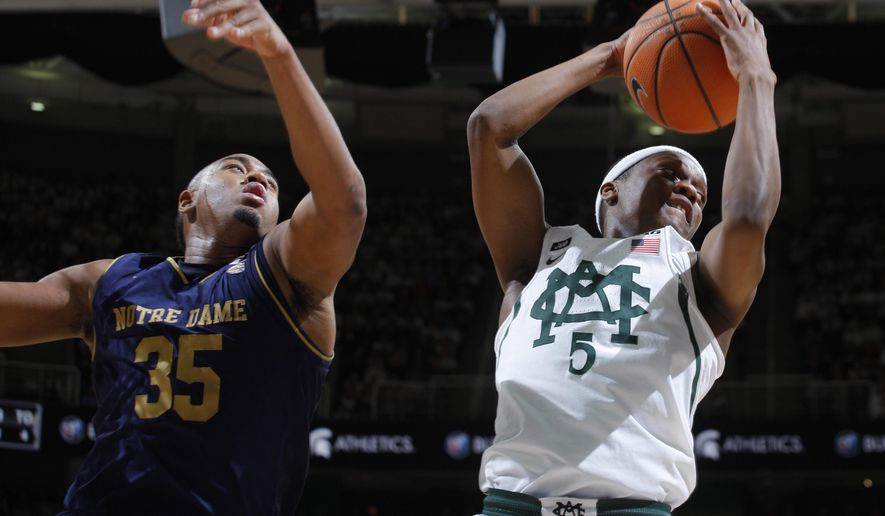 Michigan State's Cassius Winston, right, grabs a rebound against Notre Dame's Bonzie Colson (35) during the first half of an NCAA college basketball game, Thursday, Nov. 30, 2017, in East Lansing, Mich. (AP Photo/Al Goldis)