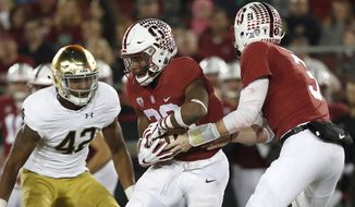FILE - In this Nov. 25, 2017, file photo, Stanford quarterback K.J. Costello (3) hands off to Stanford running back Bryce Love (20) against Notre Dame during the first half of an NCAA college football game in Stanford, Calif. The Stanford team that walked out of the Los Angeles Coliseum nearly three months ago after being overpowered by Southern California in a way perhaps no team had done to the Cardinal under David Shaw seemed an unlikely pick to get a rematch with the Trojans. Yet here Stanford is in the Pac-12 title game ready to get revenge against USC for that 42-24 loss in the second game of the season having won eight of nine games with a familiar formula. (AP Photo/Tony Avelar, File)