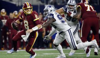 Washington Redskins quarterback Kirk Cousins (8) scrambles out of the pocket escaping pressure from Dallas Cowboys defensive end DeMarcus Lawrence in the first half of an NFL football game, Thursday, Nov. 30, 2017, in Arlington, Texas. (AP Photo/Ron Jenkins) ** FILE **