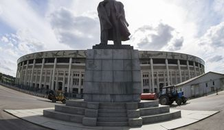 In this photo taken on Wednesday, June 28, 2017 the statue of Soviet founder stands in front of the Luzhniki stadium entrance in Moscow. The historic Luzhniki stadium, built in 1956, will host the opening and the final matches of 2018 World Cup. (AP Photo/Denis Tyrin)