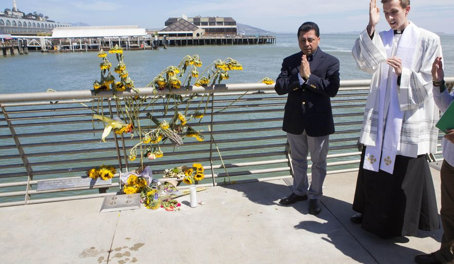 FILE - In this July 6, 2015 file photo, Father Cameron Faller, right, and Julio Escobar, of Restorative Justice Ministry, conduct a vigil for Kathryn Steinle on Pier 14 in San Francisco. A jury has reached a verdict Thursday, Nov. 30, 2017, in the trial of Mexican man at center of immigration debate in the San Francisco pier shooting. (AP Photo/Beck Diefenbach, File)