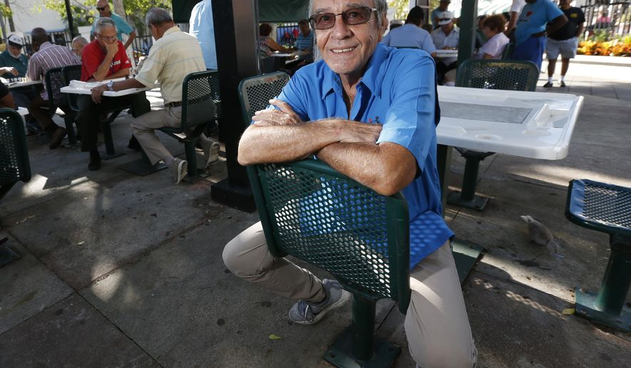 In this Wednesday, Nov. 8, 2017, photo, Associated Press photographer Alan Diaz poses at Domino Park on Calle Ocho in the Little Havana neighborhood of Miami. Diaz, whose coverage of a 6-year-old Cuban boy named Elian Gonzalez earned him the Pulitzer Prize, is retiring on Dec. 1, 2017, after 17 years with the wire service. (AP Photo/Wilfredo Lee)