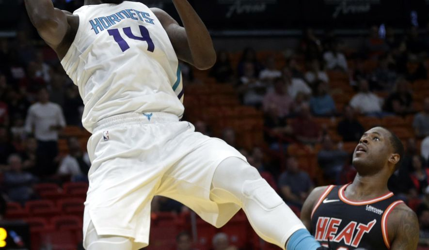 Charlotte Hornets' Michael Kidd-Gilchrist (14) passes over Miami Heat's Dion Waiters during the first half of an NBA basketball game, Friday, Dec. 1, 2017, in Miami. (AP Photo/Lynne Sladky)