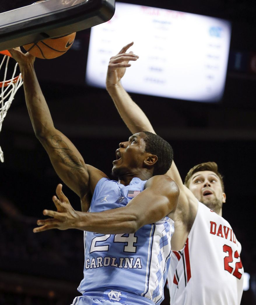 North Carolina guard Kenny Williams (24) goes up for two points while covered by Davidson forward Will Magarity (22) during the first half of an NCAA college basketball game in Charlotte, N.C., Friday, Dec. 1, 2017. (AP Photo/Jason E. Miczek)