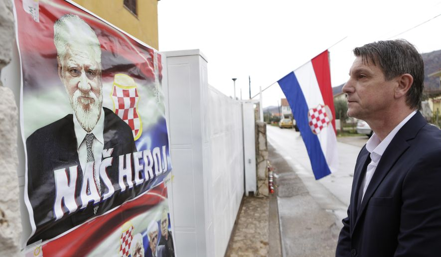 """Bosnian Croat man Pero Pervisic , 49, friend of late Gen. Praljak, pays his respect in front of house where Gen. Slobodan Praljak was born, on the house are placed posters reading """" Our Hero"""", in southern Bosnian town of Capljina 170 kms south of Sarajevo, on Thursday, Nov. 30, 2017. Gen. Praljak took his own life during sentence reading before The International War Crimes Tribunal in The Hague. Praljak was standing trial for war crimes committed in the name of Bosnian Croats, during 1992-95 war.(AP Photo/Amel Emric)"""