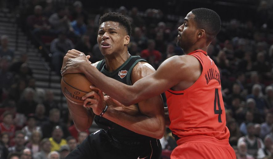 Milwaukee Bucks forward Giannis Antetokounmpo is tied up for a jump ball by Portland Trail Blazers forward Maurice Harkless, right, during the first quarter of an NBA basketball game in Portland, Ore., Thursday, Nov. 30, 2017. (AP Photo/Steve Dykes)