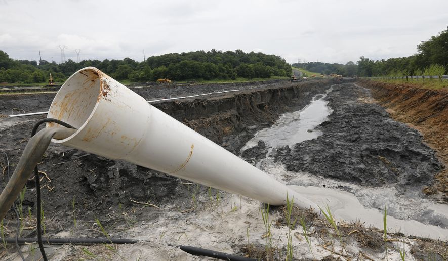 FILE - In this June 26, 2015 file photo a drain pipe sticks out of a coal ash retention pond at the Dominion Power's Possum Point Power Station in Dumfries, Va. A new report released Friday, Dec. 1, 2017,  from Dominion Energy says it would be cheaper and quicker to close and cover coal ash ponds than to recycle the waste or move it to landfills. (AP Photo/Steve Helber, File)