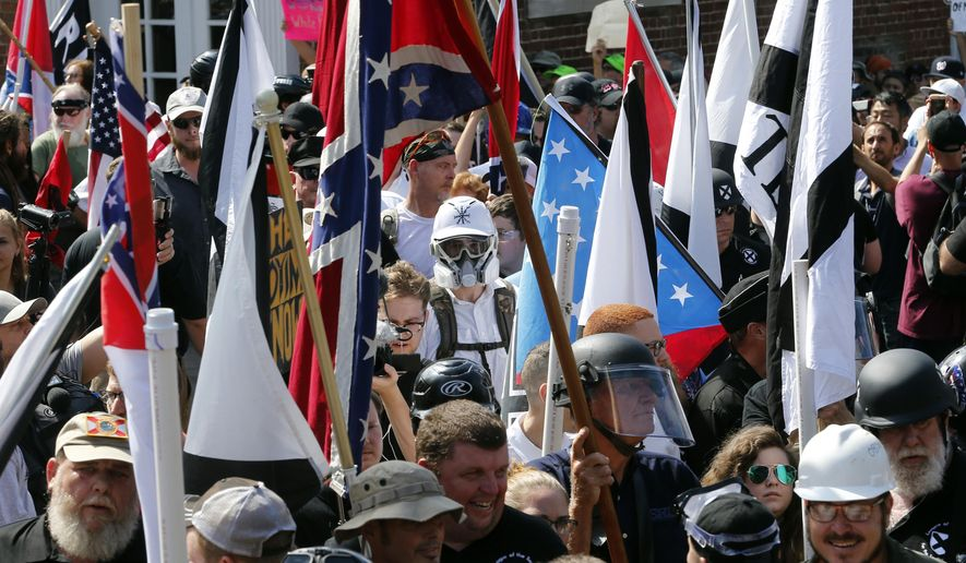 In this Saturday, Aug. 12, 2017, file photo, white nationalist demonstrators walk into the entrance of Lee Park surrounded by counter demonstrators in Charlottesville, Va. (AP Photo/Steve Helber, File)