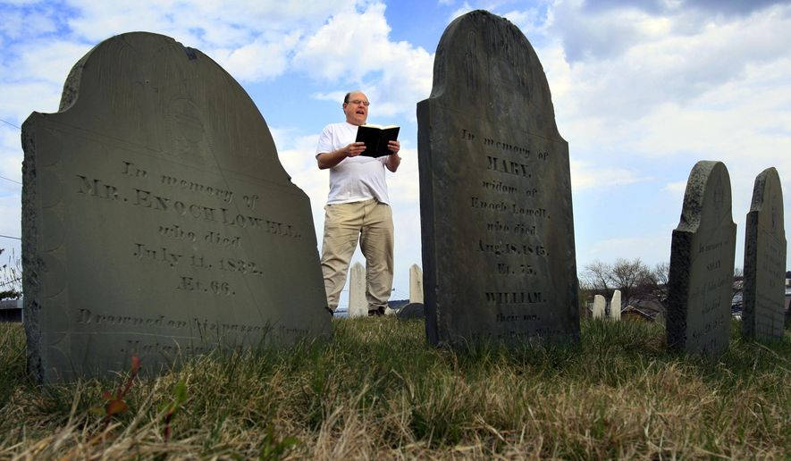 FILE - In this April 20, 2010 file photo, Walter Skold of Freeport, Maine, reads a Henry Wadsworth Longfellow poem while posing in Eastern Cemetery in Portland, Maine. Skold, the founder of the Dead Poets Society of America who has visited the graves of more than 600 bards, has commissioned John Updike's son to carve his own tombstone in 2017 in Newburyport, Mass. (AP Photo/Robert F. Bukaty, File)