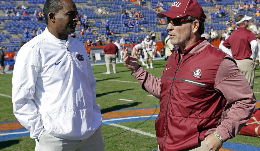Florida interim head coach Randy Shannon, left, greets Florida State head coach Jimbo Fisher at midfield before an NCAA college football game, Saturday, Nov. 25, 2017, in Gainesville, Fla. (AP Photo/John Raoux)