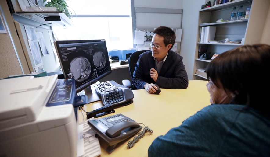 FILE - In this Aug. 15, 2017 file photo, patient Alison Cairnes, foreground, looks at images with her doctor Shumei Kato at the University of California San Diego in San Diego. Tumor profiling that sequenced Cairnes' cancer genes helped identify a treatment that proved effective for her gastric cancer. On Thursday, Nov. 30 the U.S. Food and Drug Administration approved one such test by Foundation Medicine.   (AP Photo/Gregory Bull, File)