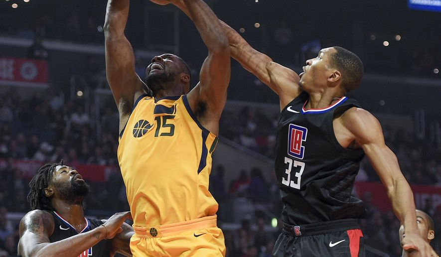 Los Angeles Clippers forward Wesley Johnson, right, blocks a shot by Utah Jazz forward Derrick Favors, center, as center DeAndre Jordan watches during the first half of an NBA basketball game in Los Angeles, Thursday, Nov. 30, 2017. (AP Photo/Kelvin Kuo)