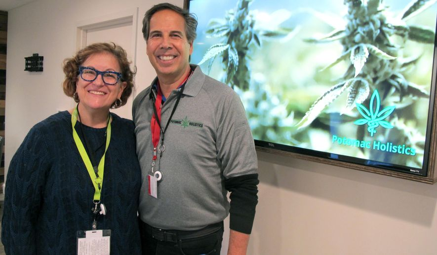 Louise Fisher and William Askinazi, who are co-owners of a medical marijuana dispensary called Potomac Holistics, stand in the store in Rockville, Md., on Friday, Dec. 1, 2017, hours before they were scheduled to receive their first shipment and begin selling medical marijuana, among the first dispensaries in the state to do so. (AP Photo/Brian Witte)