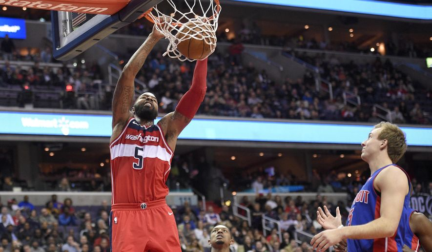 Washington Wizards forward Markieff Morris, left, dunks in front of Detroit Pistons guard Luke Kennard, right, during the second half of an NBA basketball game, Friday, Dec. 1, 2017, in Washington. Wizards guard Bradley Beal is at center. The Wizards won 109-91. (AP Photo/Nick Wass)