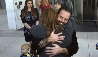 Nevada ranching standoff defendant Ryan Payne, facing camera, hugs a friend outside the U.S. District Courthouse in Las Vegas following his release on Friday, Dec. 1, 2017, after 22 months in federal custody. Payne, 34, of Anaconda, Mont., was arrested in 2016 in Oregon following an occupation of a federal wildlife refuge. He is standing trial with Nevada rancher Cliven Bundy and two Bundy sons in a 2014 armed confrontation with federal agents. (AP Photo/Ken Ritter)