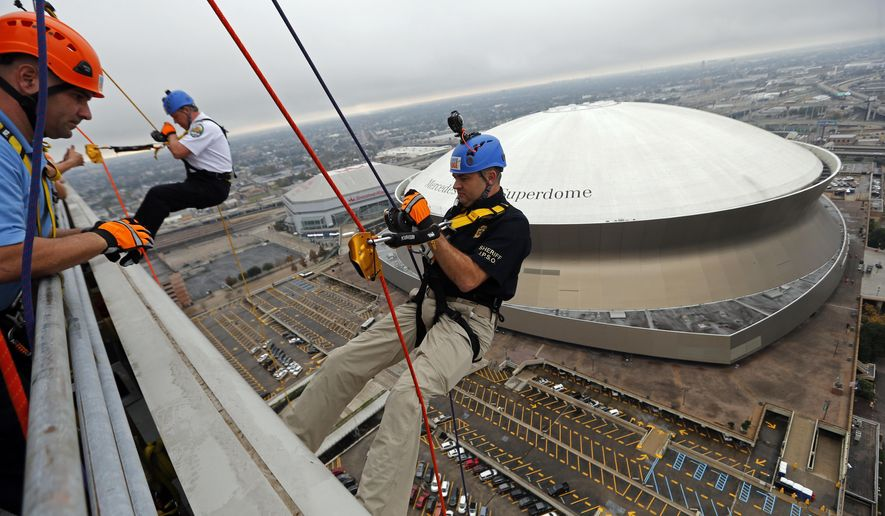 """Kenner, La. Police Chief Michael J. Glaser, left, Jefferson Parish Sheriff Joe Lopinto, rappel down the side of the 26-story Benson Tower, as part of a challenge to raise awareness for a fundraiser for Special Olympics Louisiana, in downtown New Orleans, Thursday, Nov. 30, 2017. Donors who give $1,000 or more to the charity will be rappelling down the side of the building on Friday. The day-long event, called """"Over the Edge NOLA: S.W.A.T. Edition,"""" is being co-hosted by the two Police Departments, which are providing helicopters and safety and security personnel for the event. Participants who qualify will have the opportunity to take a helicopter ride, rappel down the side of Benson Tower and """"S.W.A.T. train"""" at the Jefferson Parish Sheriff's Training Facility. (AP Photo/Gerald Herbert)"""