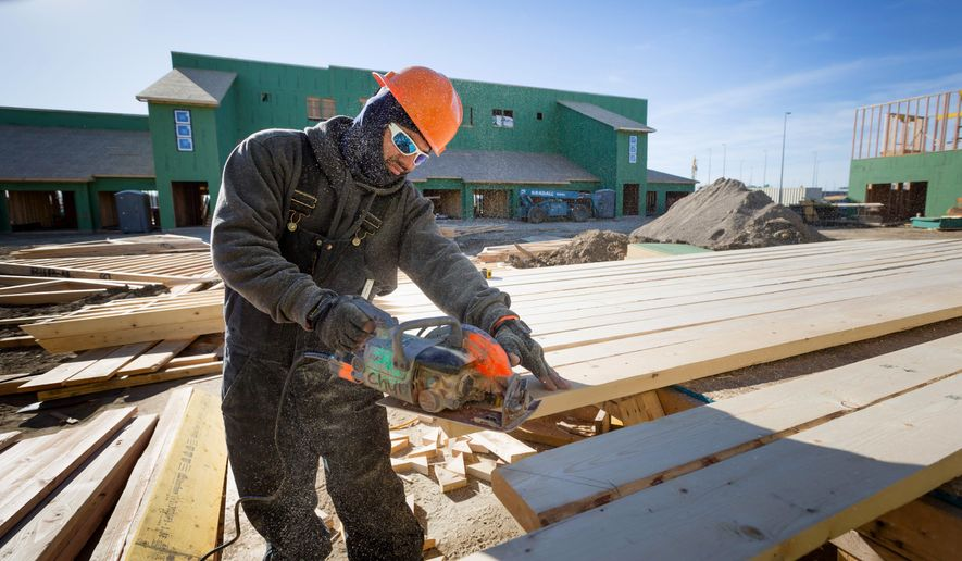 In this Wednesday, Nov. 29, 2017 photo, Geronimo Lopez cuts lumber for the new construction at the River's Edge redevelopment area in Council Bluffs, Iowa. (Kent Sievers/Omaha World-Herald via AP)