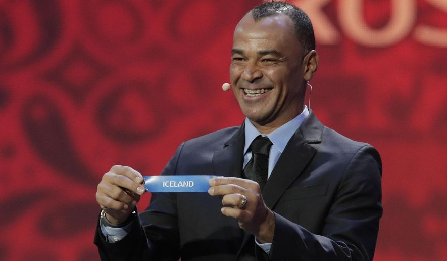 Former Brazilian soccer international Cafu holds up the team name of Iceland during the 2018 soccer World Cup draw in the Kremlin in Moscow, Friday, Dec. 1, 2017. (AP Photo/Dmitri Lovetsky)