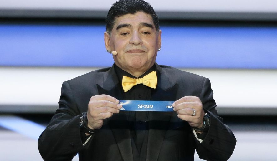 Argentine soccer legend Diego Maradona holds up the team name of Spain at the 2018 soccer World Cup draw in the Kremlin in Moscow, Friday, Dec. 1, 2017. (AP Photo/Ivan Sekretarev)