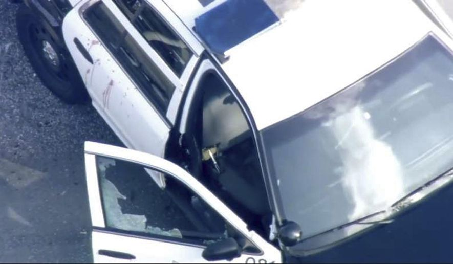 In this image provided courtesy of KTVU-TV is a San Francisco police patrol car with a shattered front passenger window and blood splattered on a side door at a shooting scene Friday, Dec. 1, 2017, in San Francisco. San Francisco police are investigating the officer-involved shooting in the city's Bayview neighborhood. (Courtesy of KTVU-TV via AP)